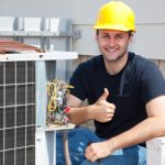 Air conditioning repairman working on a compressor and giving a thumbsup.